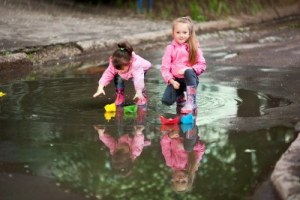 13989386-little-girls-wearing-a-pink-jacket-playing-with-colorful-paper-ship-in-the-puddle