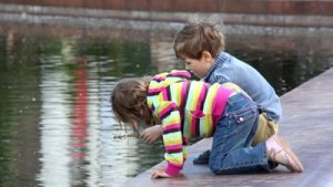 stock-footage-boy-and-girl-playing-fishing-at-the-city-pond